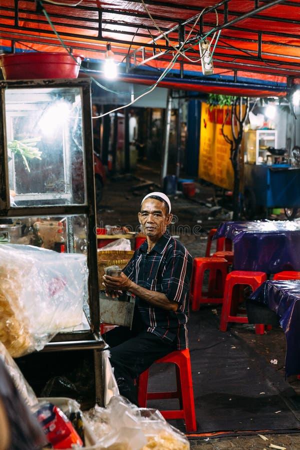 El viejo hombre musulmán que vende a Mie Goreng en el mercado de la noche se sienta en la parte posterior de su vendedor ambulant foto de archivo libre de regalías