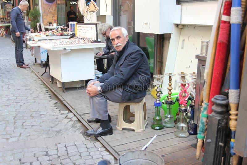 El viejo hombre que vende la cachimba instala tubos en la calle en Estambul, Turquía foto de archivo