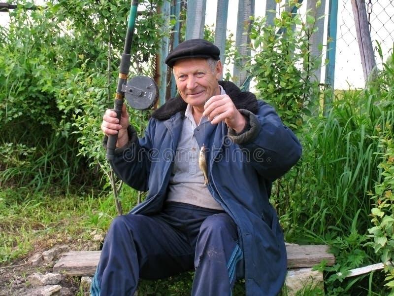 El viejo hombre rural se jacta un pequeño pescado cogido fotos de archivo