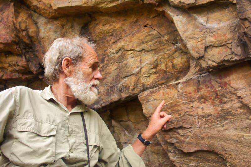 El viejo hombre señala en las pinturas antiguas del bosquimano foto de archivo libre de regalías