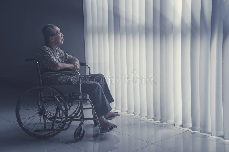 El viejo hombre se sienta en la silla de ruedas mientras que sueña despierto foto de archivo libre de regalías