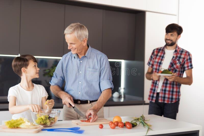 El viejo hombre y el muchacho están preparando una ensalada El padre del ` s del muchacho les trajo más verduras imagenes de archivo