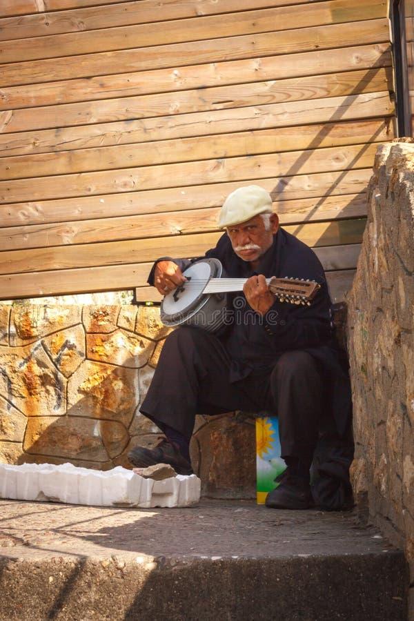 El viejo músico turco de la calle juega el baglama imagenes de archivo