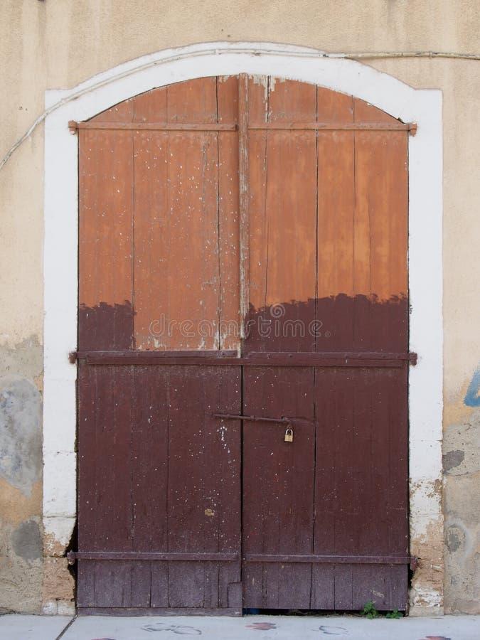 El viejo marrón de decaimiento pintoresco pintó puertas dobles de madera empernadas cerradas con un candado fijado en un marco de foto de archivo