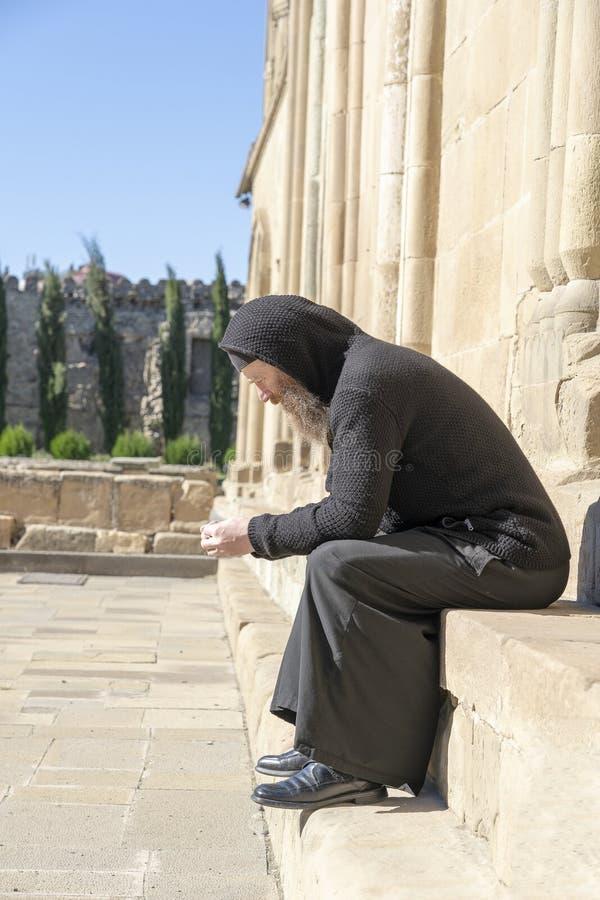 El viejo monje solo en ropa negra se sienta en las escaleras cerca de la catedral ortodoxa vieja en la ciudad Mtskheta cerca de T fotos de archivo