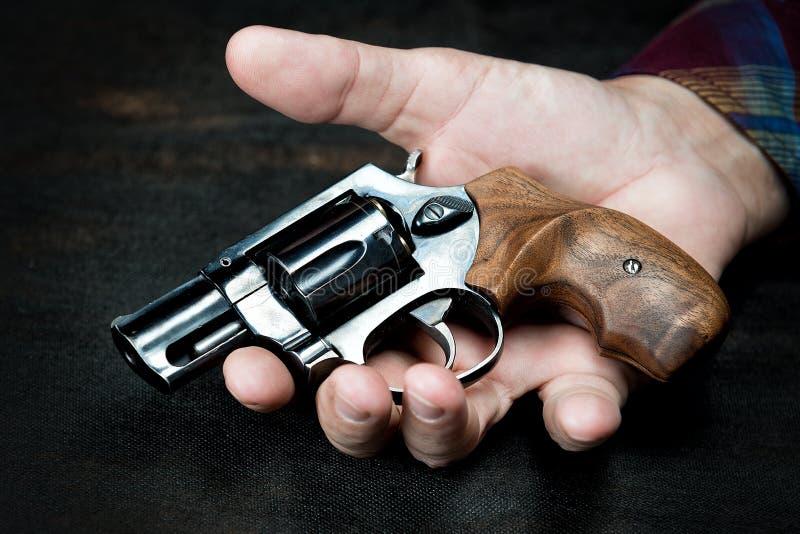 El viejo pequeño revólver miente en una mano del ` s del hombre imagen de archivo libre de regalías