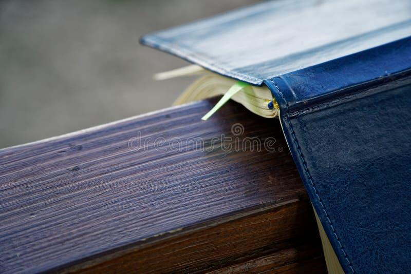 El viento da vuelta a las páginas de las mentiras abiertas del cuaderno en la barandilla de madera en parque, concepto del negoci foto de archivo libre de regalías