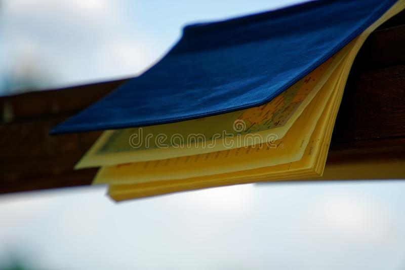 El viento da vuelta a las páginas de las mentiras abiertas del cuaderno en la barandilla de madera en parque, concepto del negoci fotografía de archivo libre de regalías