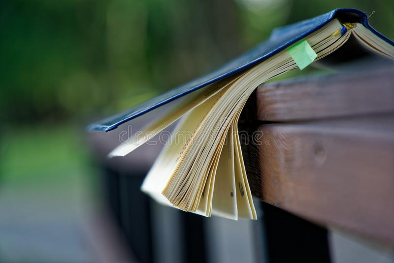 El viento da vuelta a las páginas de las mentiras abiertas del cuaderno en la barandilla de madera en parque, concepto del negoci fotos de archivo