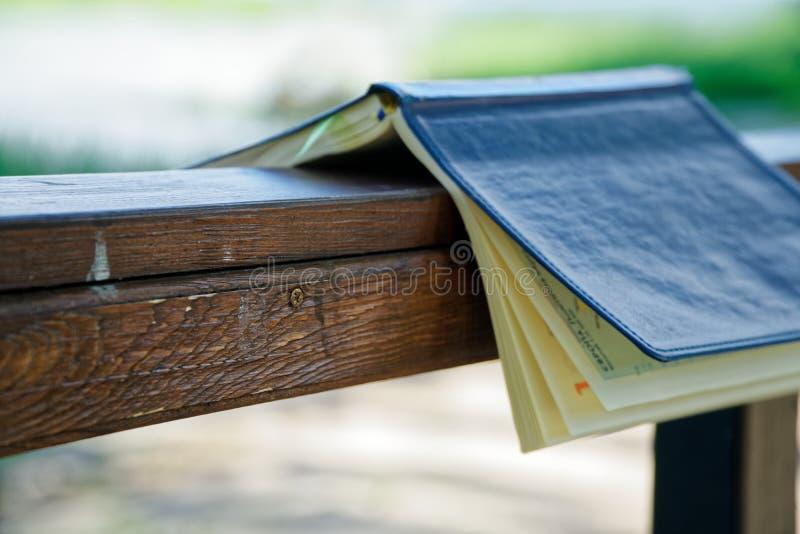 El viento da vuelta a las páginas de las mentiras abiertas del cuaderno en la barandilla de madera en parque, concepto del negoci foto de archivo