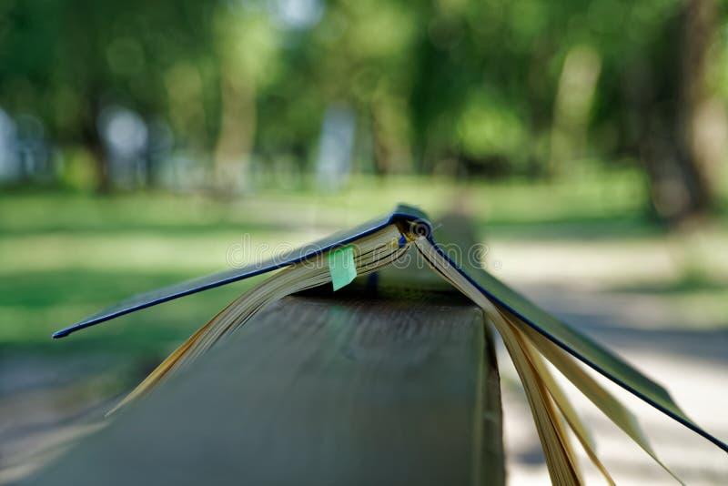 El viento da vuelta a las páginas de las mentiras abiertas del cuaderno en la barandilla de madera en parque, concepto del negoci fotografía de archivo