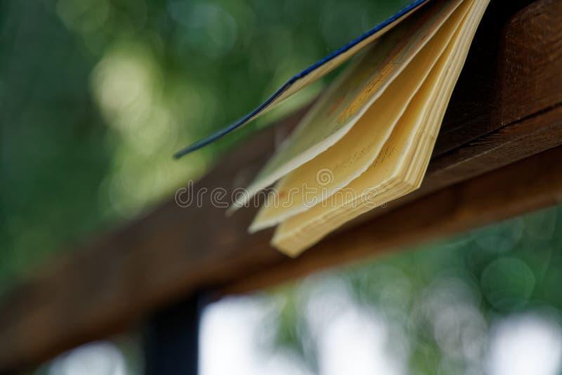 El viento da vuelta a las páginas de las mentiras abiertas del cuaderno en la barandilla de madera en parque, concepto del negoci imagenes de archivo