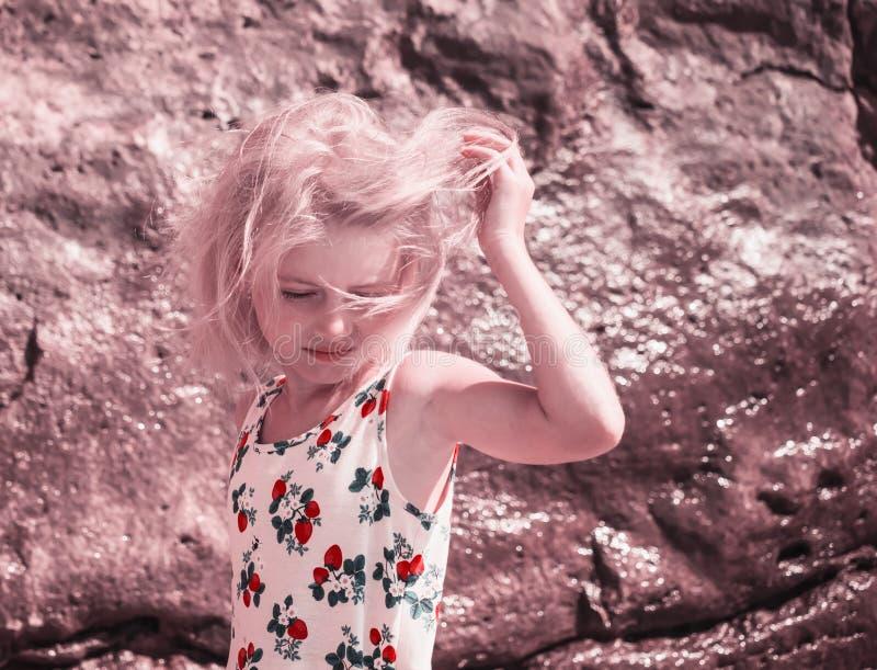 El viento est? jugando el pelo en muchacha rubia en la playa fotografía de archivo