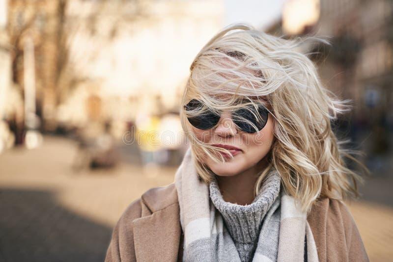 El viento sopla el pelo rubio de la señora y cubre su cara y gafas de sol foto de archivo libre de regalías