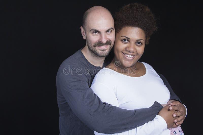 El vientre de la madre de caricia de los pares interraciales jovenes imagenes de archivo