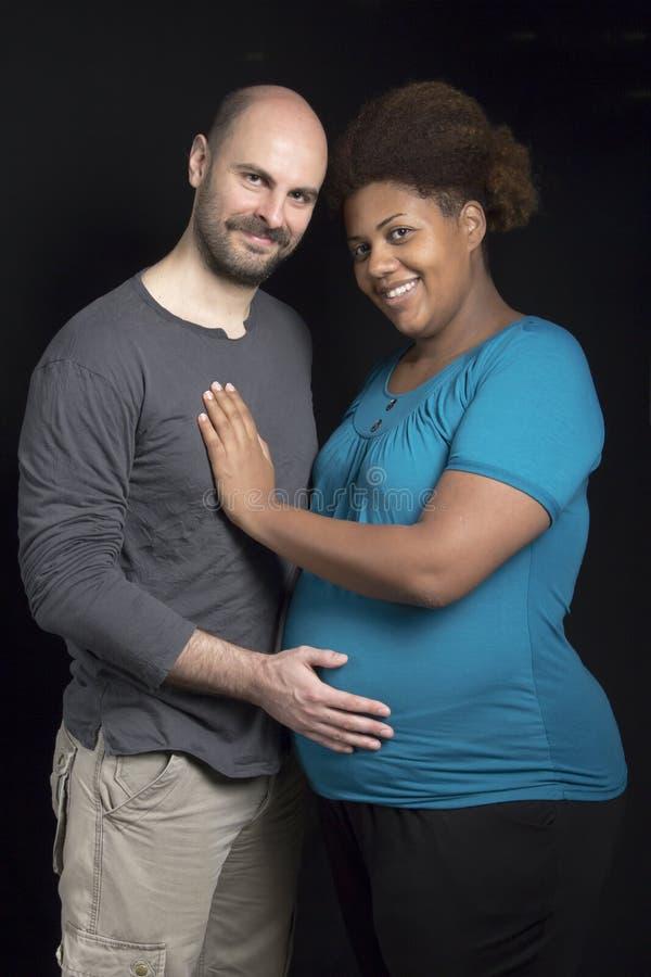El vientre de la madre de caricia de los pares interraciales jovenes imágenes de archivo libres de regalías