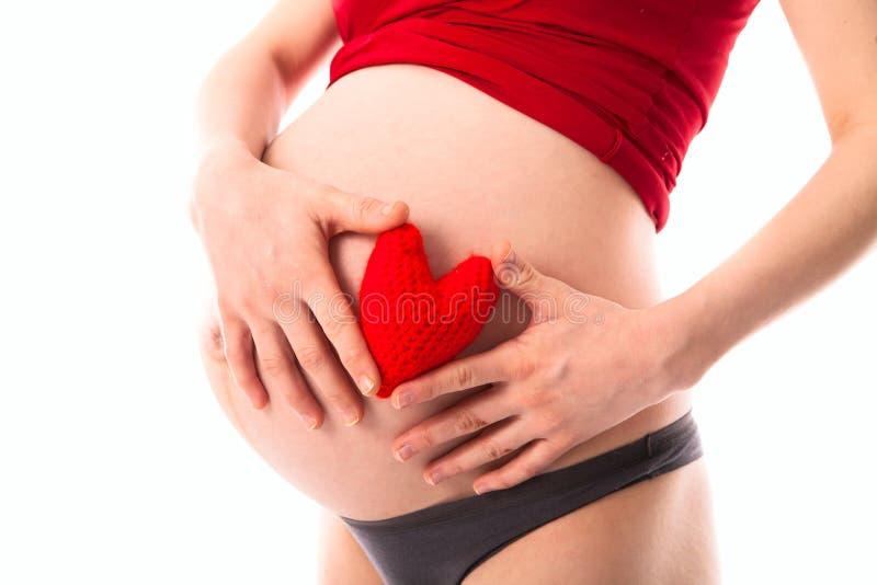 El vientre de la mujer embarazada con rojo hizo punto el corazón, concepto de amor, imágenes de archivo libres de regalías