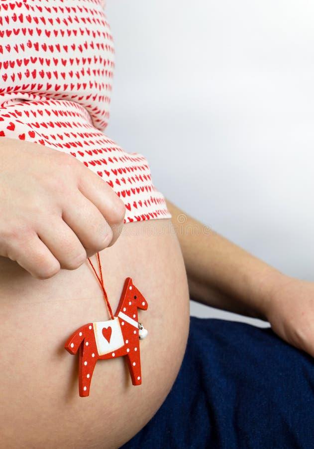 El vientre de la mujer embarazada con un juguete del caballo fotografía de archivo libre de regalías