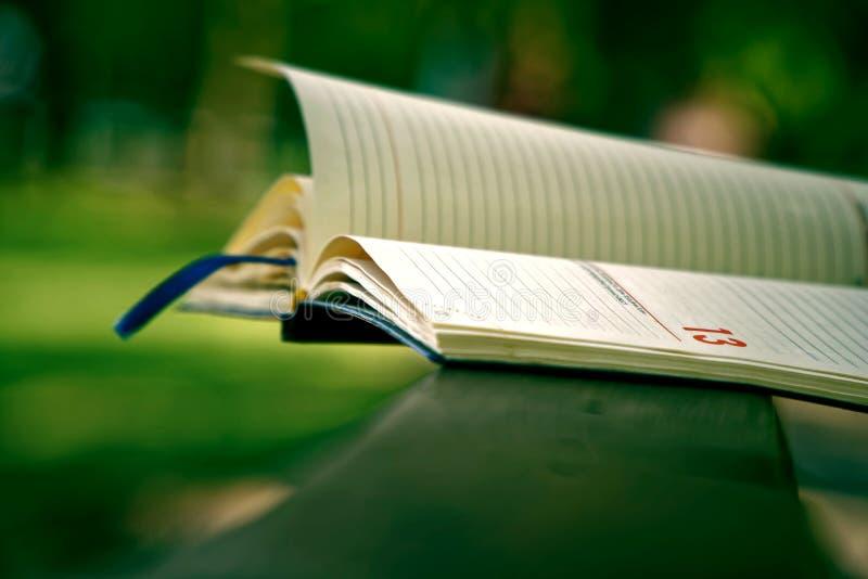 El viernes 13, viento da vuelta a las páginas de las mentiras abiertas del cuaderno en la barandilla de madera en parque, concept fotografía de archivo libre de regalías