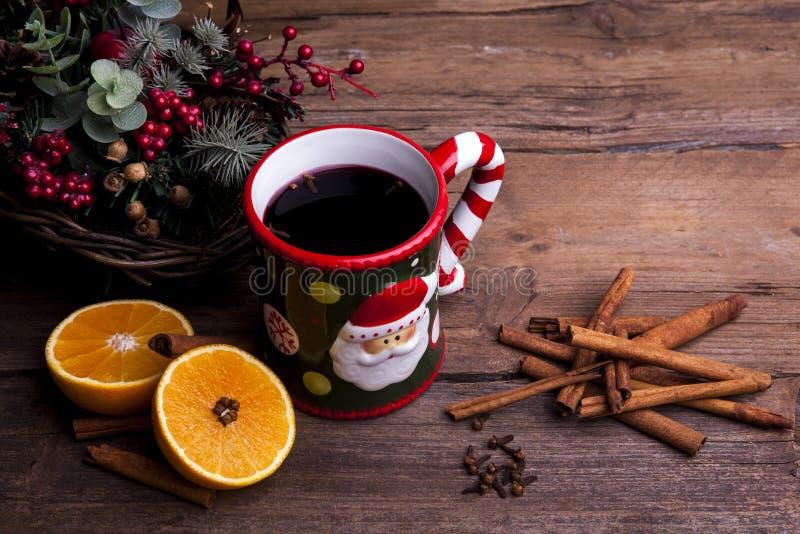 El vino reflexionado sobre con las decoraciones de la Navidad tiradas en un fondo de madera pescó con caña fotografía de archivo