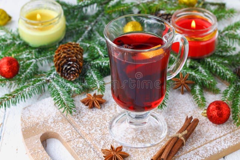 El vino reflexionado sobre del Año Nuevo en un vidrio en el fondo de ramitas, de velas y de guirnaldas imágenes de archivo libres de regalías