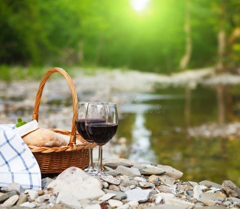 El vino rojo, el queso y el pan sirvieron en una comida campestre imágenes de archivo libres de regalías