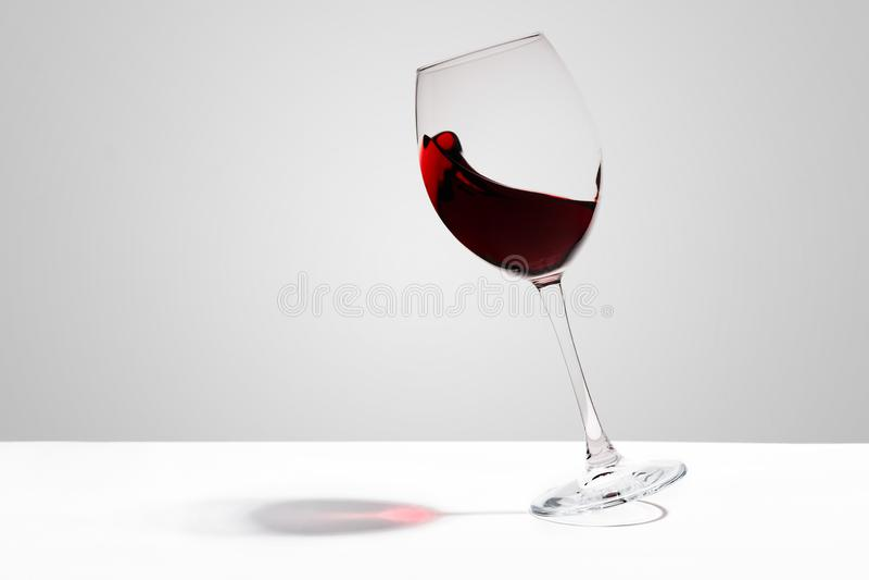 El vino rojo salpica en un vidrio en el fondo blanco imagenes de archivo