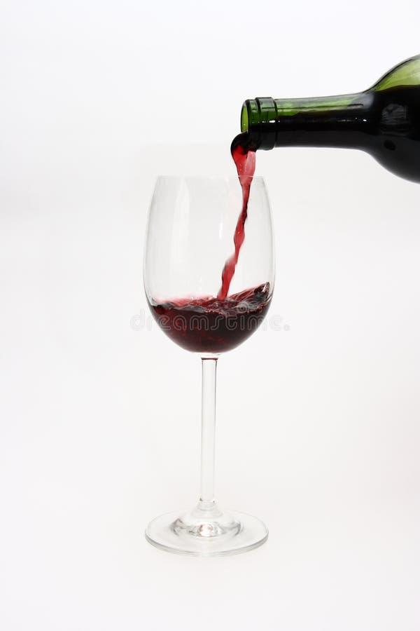 El vino rojo vertió en un vidrio foto de archivo