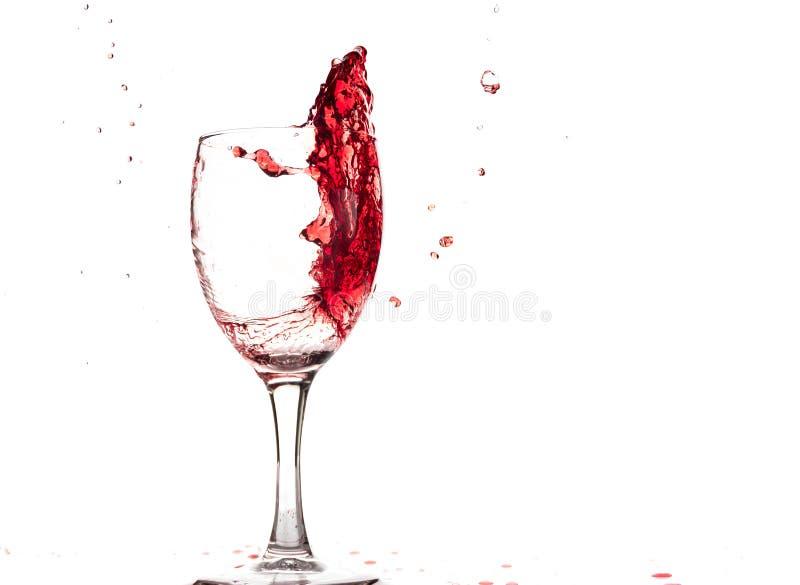 El vino tinto cae en un vidrio y crea el chapoteo y salpica en un fondo blanco imagen de archivo