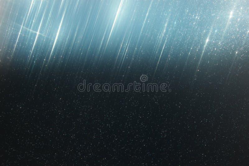 El vintage del brillo enciende el fondo azul marino ligero y oro defocused foto de archivo