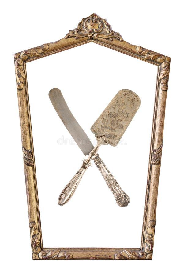 El vintage doró el marco pentagonal y cruzó la pala y el cuchillo de la torta con un ornamento aislado en blanco Estilo retro fotos de archivo libres de regalías