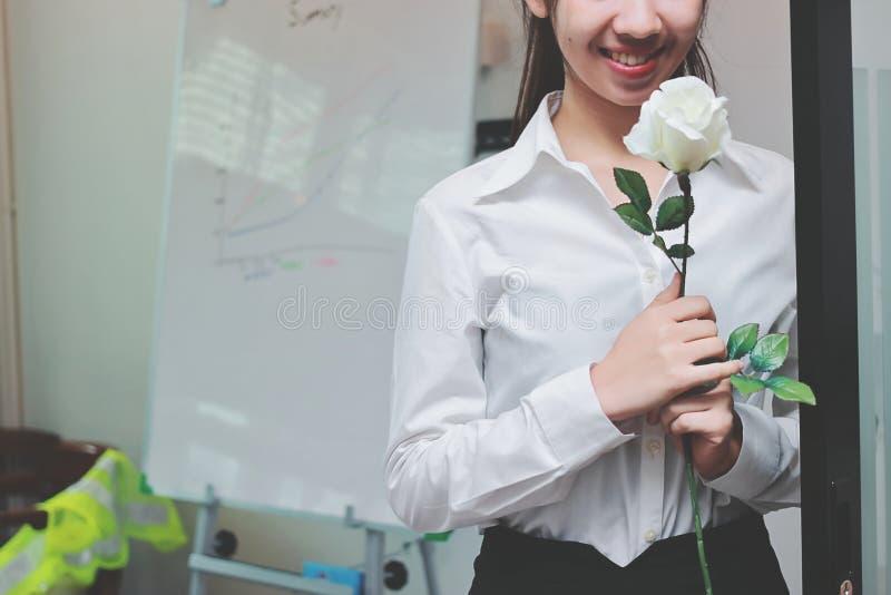 El vintage entonó imagen de la mujer de negocios asiática joven alegre sosteniendo las rosas blancas en oficina el día del ` s de foto de archivo libre de regalías