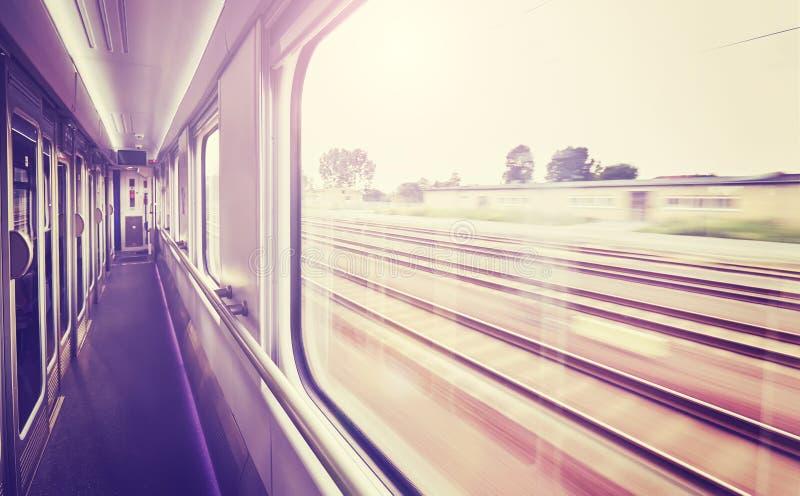 El vintage entonó la ventana del tren con los carriles borrosos afuera foto de archivo