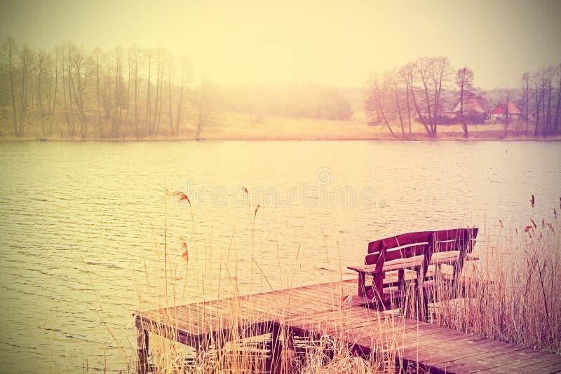 El vintage estilizó la foto del banco en el lago foto de archivo libre de regalías