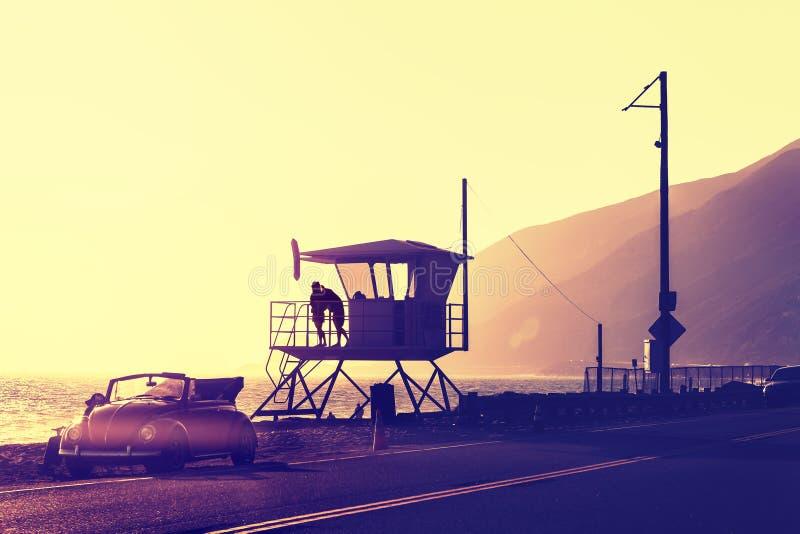 El vintage filtró puesta del sol sobre la playa con la torre del salvavidas imágenes de archivo libres de regalías