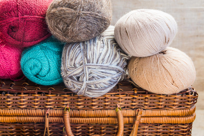 El vintage hace el pecho a mano de mimbre, ovillos, bolas del hilado de lanas multicolor, concepto gris, que hace punto beige bla imágenes de archivo libres de regalías