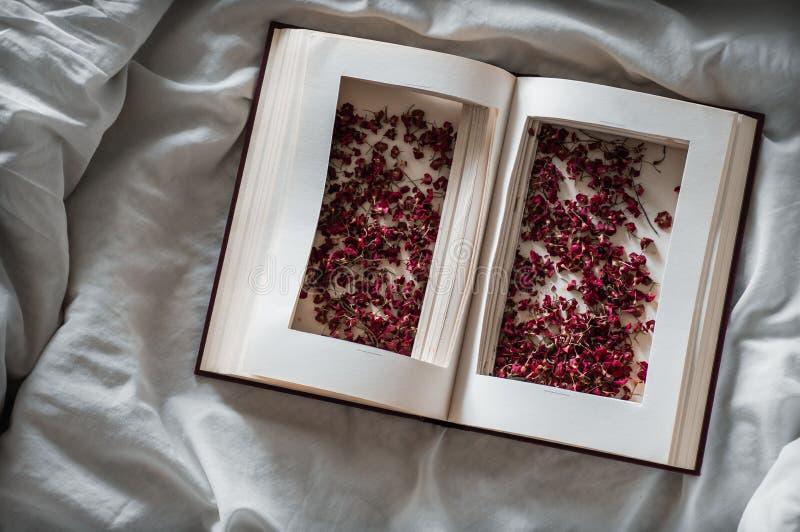 El vintage reserva con las flores rojas secadas en una cama blanca Nostálgico del concepto y fondo del vintage de la conmemoració fotografía de archivo libre de regalías