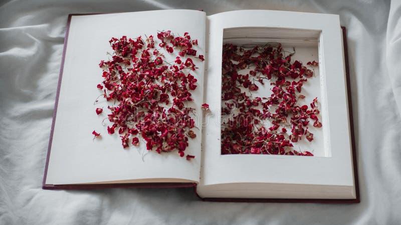 El vintage reserva con las flores rojas secadas en una cama blanca Nostálgico del concepto y fondo del vintage de la conmemoració foto de archivo