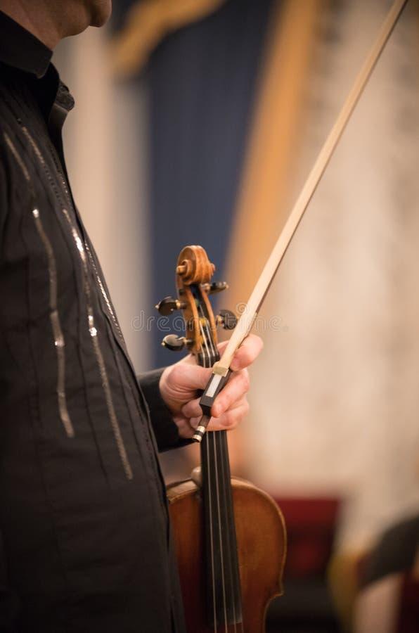 El violinista sostiene el violín en la sala de conciertos imagen de archivo