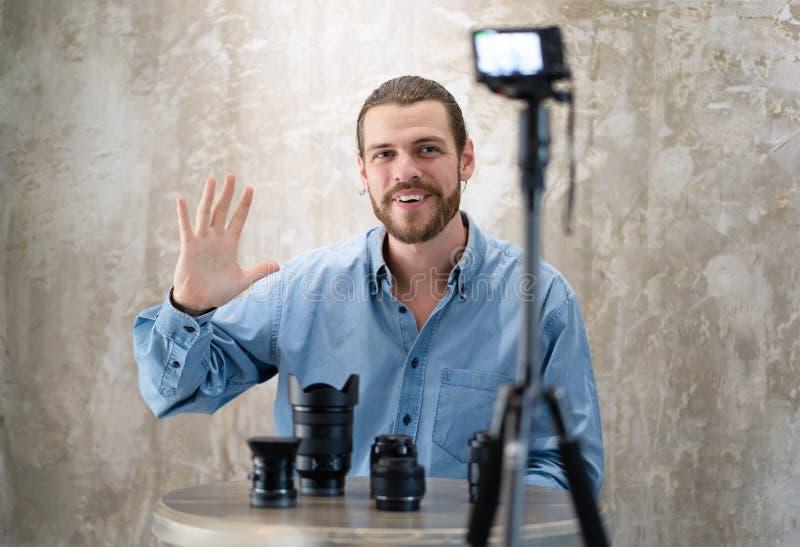 El vlogger joven del inconformista est? mostrando la colecci?n de lente de c?mara mientras que bloguean los consejos de registrac imagen de archivo libre de regalías