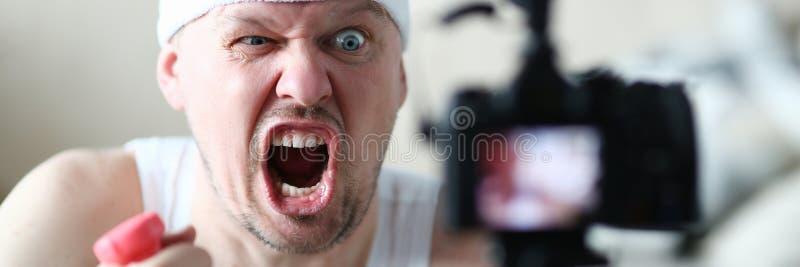 El vlogger masculino lleva a cabo pesas de gimnasia en el suyo imagen de archivo libre de regalías