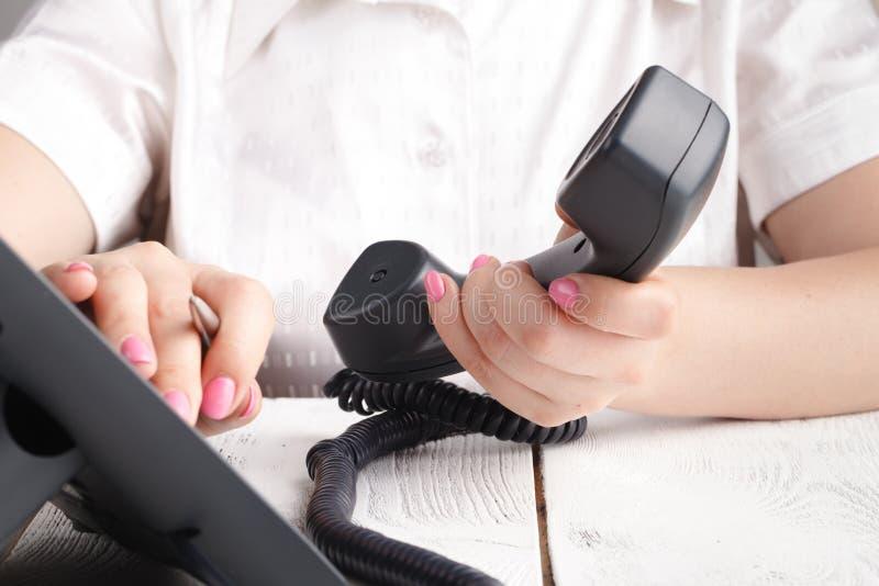 El voip de marca llama por teléfono en el detalle de la oficina, del teclado y del monitor en el fondo fotos de archivo