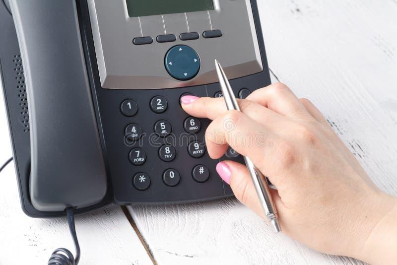 El voip de marca llama por teléfono en el detalle de la oficina, del teclado y del monitor en el fondo fotografía de archivo libre de regalías