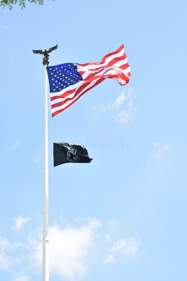 El volar de las banderas del americano y del PRISIONERO DE GUERRA fotografía de archivo libre de regalías