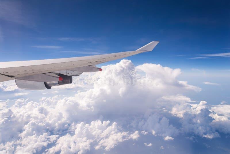 El volar en el cielo azul y el mar de nubes y del ala del aeroplano con foto de archivo