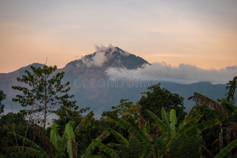 El volcán, montaña cubrió el bosque, cielo con las nubes, rastros de lava en la tierra Volcán de Batur del soporte en Kintamani imagenes de archivo