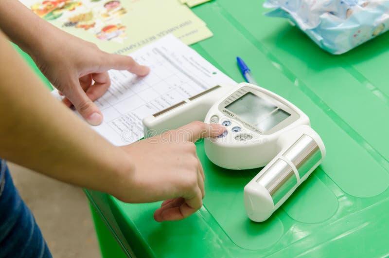 El voluntario femenino está estudiando medidas del monitor de la medida de las grasas de cuerpo en programa de salud pública libr imagenes de archivo