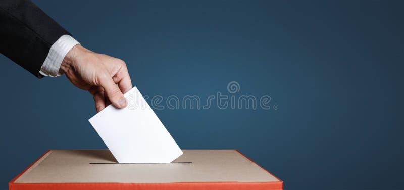 El votante lleva a cabo la votación antedicha disponible del voto del sobre en fondo azul Concepto de la democracia de la liberta imágenes de archivo libres de regalías