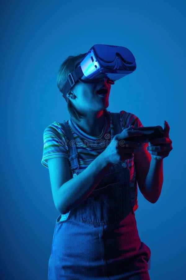 El vr del juego La muchacha en el casco y el regulador juega a un juego con la luz creativa concepto de deportes cibernéticos jue imágenes de archivo libres de regalías