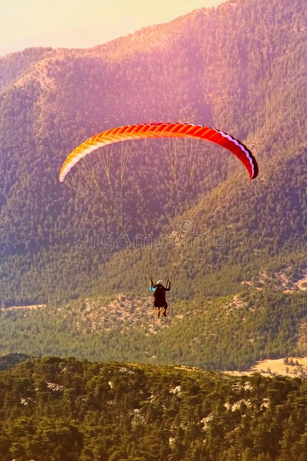 El vuelo de alas flexibles en las montañas Paragliding en el amanecer Tomar las fotos de una altura fotografía de archivo libre de regalías